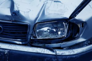 blue sedan with smashed front headlight after car accident | Hal Waldman & Associates