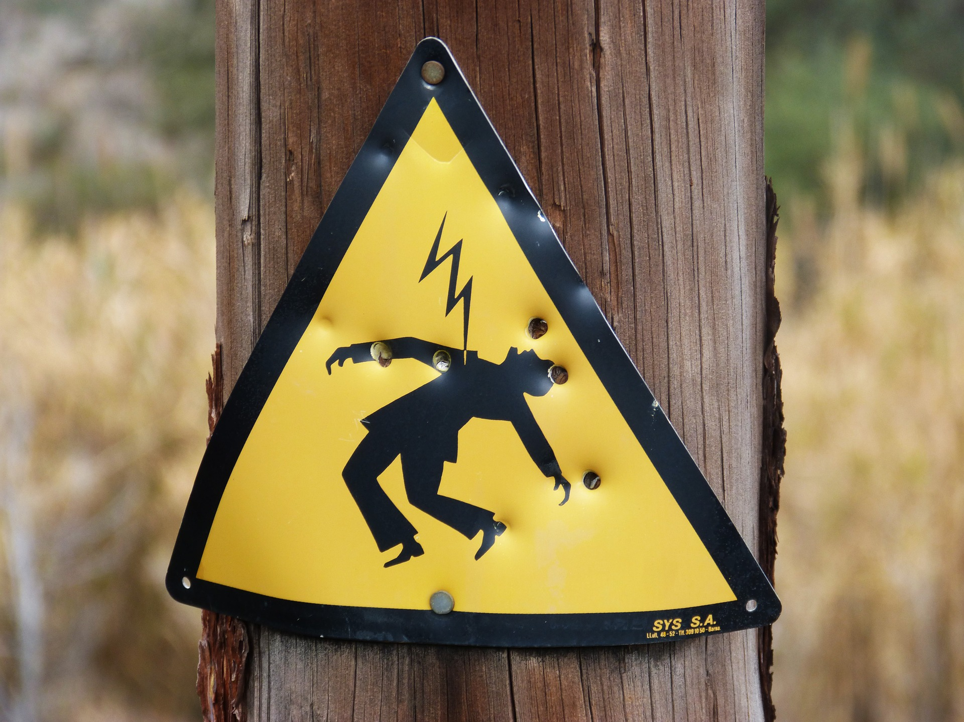 triangular yellow electrical shock sign stapled onto a brown wooden pole